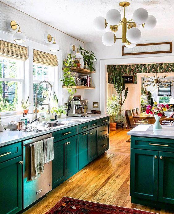 un espace super lumineux avec des armoires turquoise, des comptoirs et des murs en pierre blanche, des touches d'or