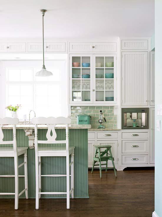 une cuisine traditionnelle faite avec des armoires et des meubles blancs, avec un îlot de cuisine vert et un dosseret de carreaux pour une touche de couleur