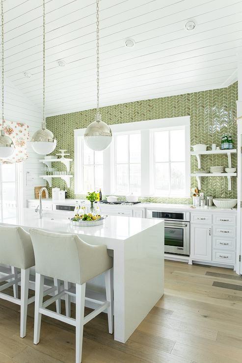 une cuisine accueillante avec des armoires blanches, un îlot de cuisine en pierre blanche, un mur de carreaux verts et des touches de nuances métalliques