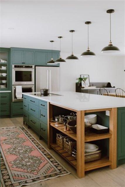 une cuisine traditionnelle faite en vert, avec des comptoirs blancs, des lampes noires et un tapis boho pour un look chic