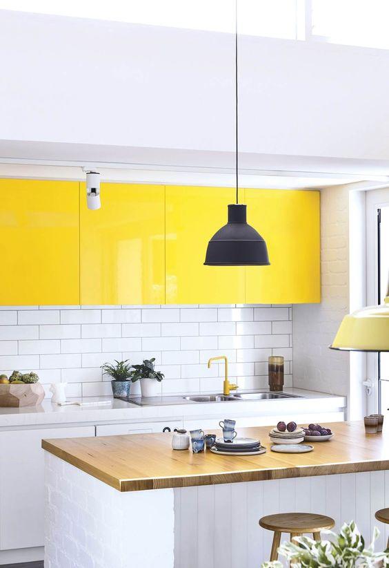 une cuisine contemporaine audacieuse faite en blanc, avec des armoires supérieures jaune vif, un comptoir en bois et un dosseret de carreaux de métro blanc