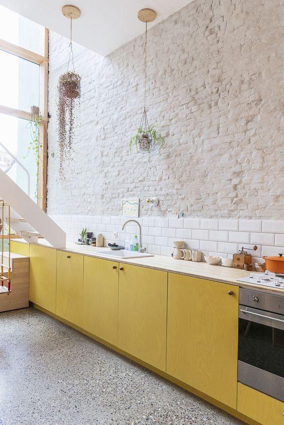 une cuisine contemporaine audacieuse avec des armoires en contreplaqué jaune, des comptoirs neutres, un dosseret de carreaux de métro blanc et un mur de briques