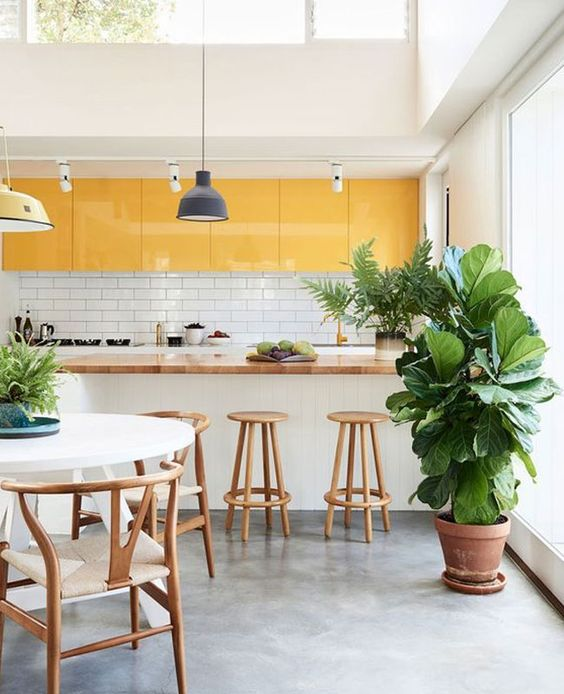 une cuisine tropicale lumineuse faite avec des armoires supérieures jaunes et tout blanc plus une lucarne pour un rafraîchissement