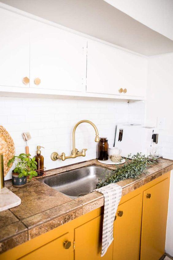 une cuisine chic avec des armoires supérieures blanches et des armoires inférieures en crème au beurre ainsi qu'un comptoir en pierre et des touches de laiton a l'air cool