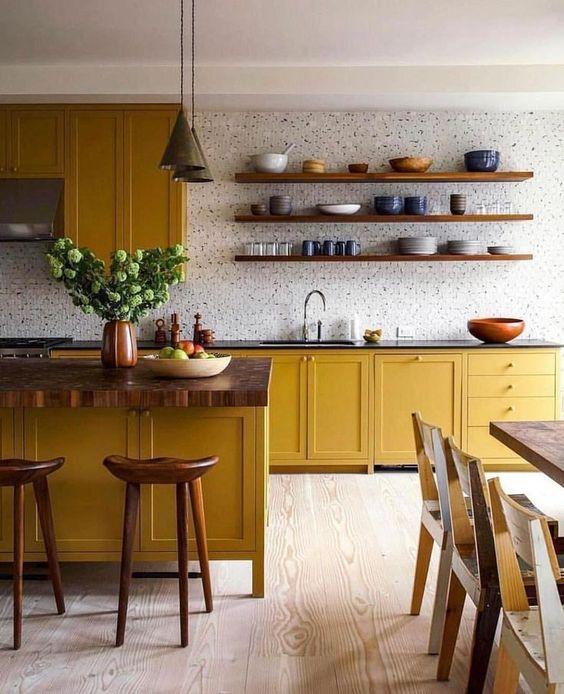 une cuisine audacieuse avec des armoires moutarde, des comptoirs en bois, un dosseret de carreaux blancs et des touches de bois ici et là