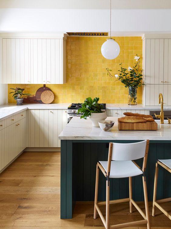 une cuisine lumineuse avec des armoires en planches blanches, un dosseret de carreaux jaunes et un îlot de cuisine bleu sarcelle avec des comptoirs en pierre