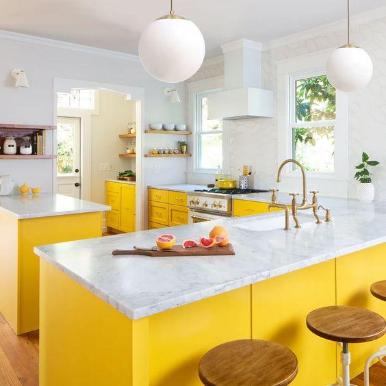 une cuisine lumineuse faite avec des armoires jaunes, des comptoirs en pierre blanche et tout blanc pour un look chic et audacieux