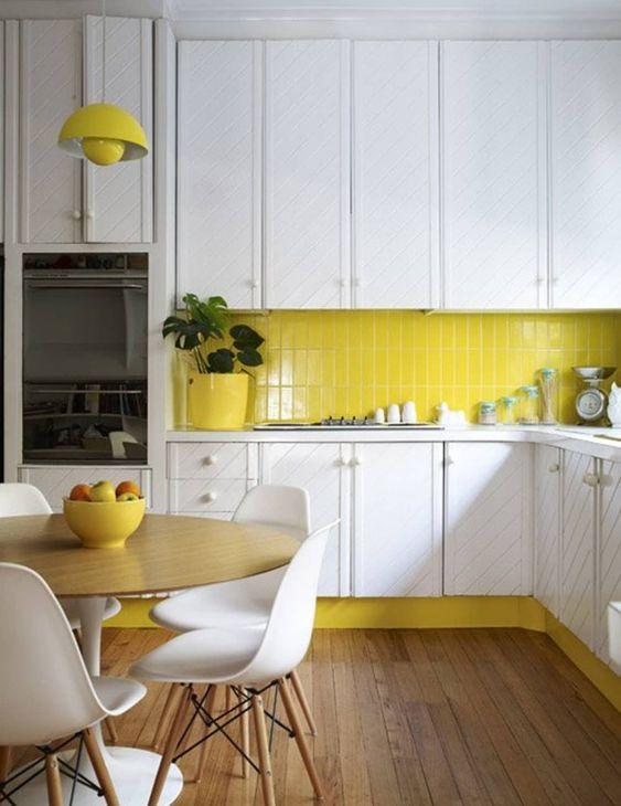 une cuisine contemporaine faite en jaune citron et blanc, avec des armoires texturées et un plancher en bois semble audacieuse