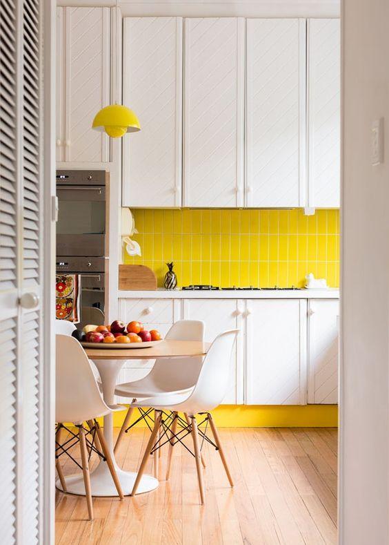 une cuisine contemporaine avec des armoires blanches, un dosseret de carreaux jaune vif et une lampe, des chaises blanches et des tons neutres