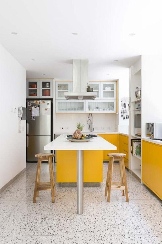 une cuisine contemporaine faite avec des armoires jaunes et blanches ensoleillées, avec des comptoirs blancs et un sol en mosaïque a l'air cool