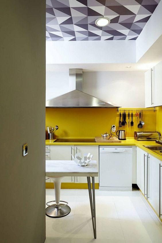 une cuisine blanche contemporaine rendue audacieuse avec un dosseret et des comptoirs jaunes ainsi que des appareils électroménagers en acier inoxydable
