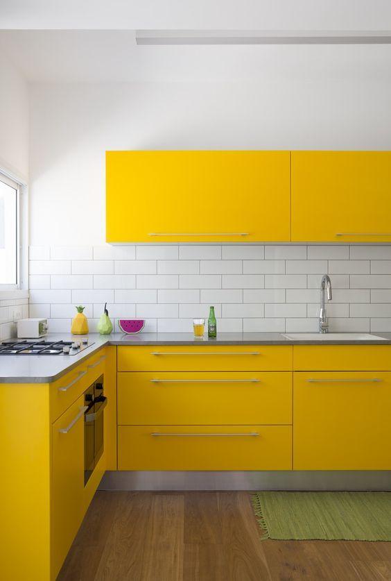 une cuisine contemporaine super lumineuse avec des armoires jaunes, un dosseret de carreaux de métro blanc et un plancher en bois a l'air wow