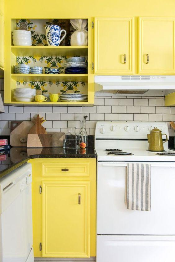 une cuisine rétro faite en blanc et jaune, avec des appareils blancs et un dosseret de carreaux de métro blanc et des comptoirs noirs