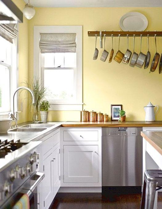 une cuisine rétro avec un mur jaune citron, des armoires blanches, des électroménagers en métal et des touches de cuivre