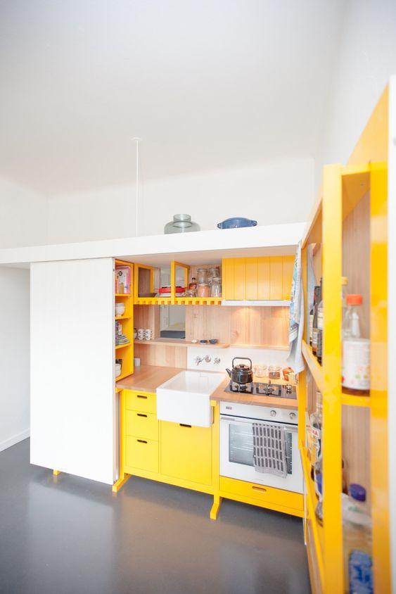 une mini cuisine contemporaine faite en jaune ensoleillé et avec des touches de bois naturel et des encastrés est audacieuse