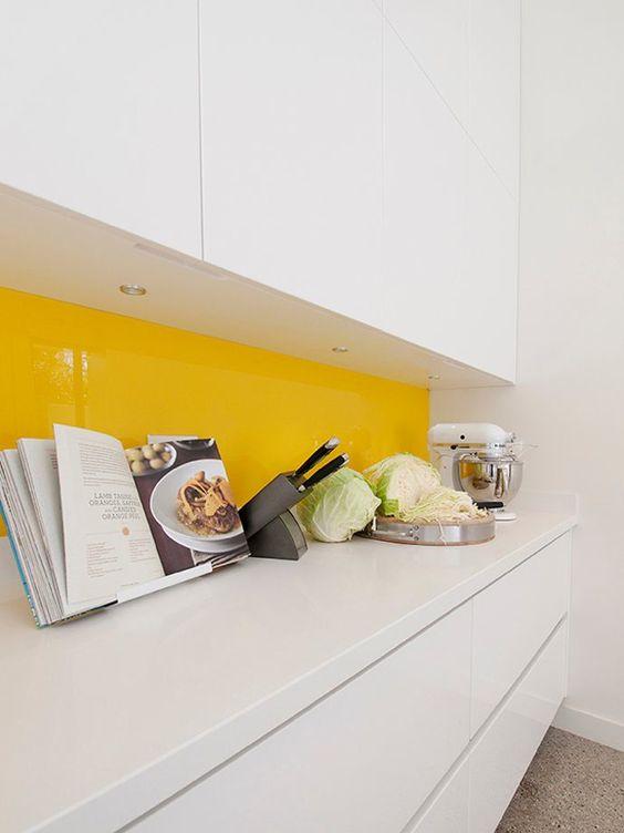 un ktichen blanc minimaliste avec un dosseret de verre jaune vif est super cool et très audacieux