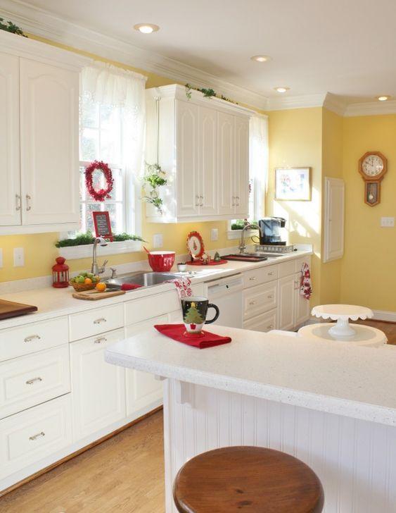 une cuisine vintage blanche avec un dosseret jaune ensoleillé et un mur d'accent, des touches de verdure rouge et fraîche