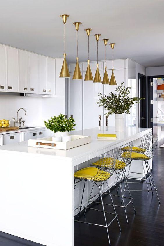 une cuisine blanche faite avec de légers accents jaunes - des tabourets jaunes et des citrons dans un bol plus des lampes dorées sur l'île