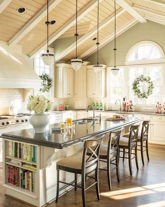 une cuisine de ferme blanche avec un grand îlot de cuisine qui comprend des rangements et un coin salon pour manger ici