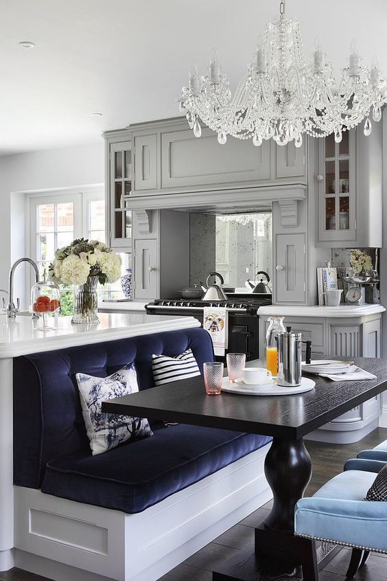 une cuisine éclectique avec des meubles gris, un îlot de cuisine blanc avec un siège marine intégré pour composer un espace salle à manger
