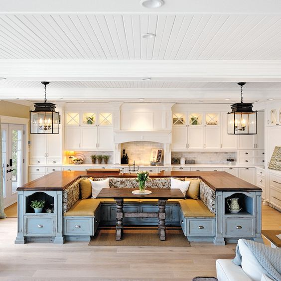 une cuisine de ferme en blanc avec un îlot de cuisine bleu qui comprend des rangements et un coin salon