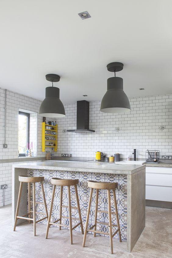 une cuisine ultra-moderne faite avec des carreaux de métro blancs, un îlot de cuisine en béton avec un espace salon pour dîner ici