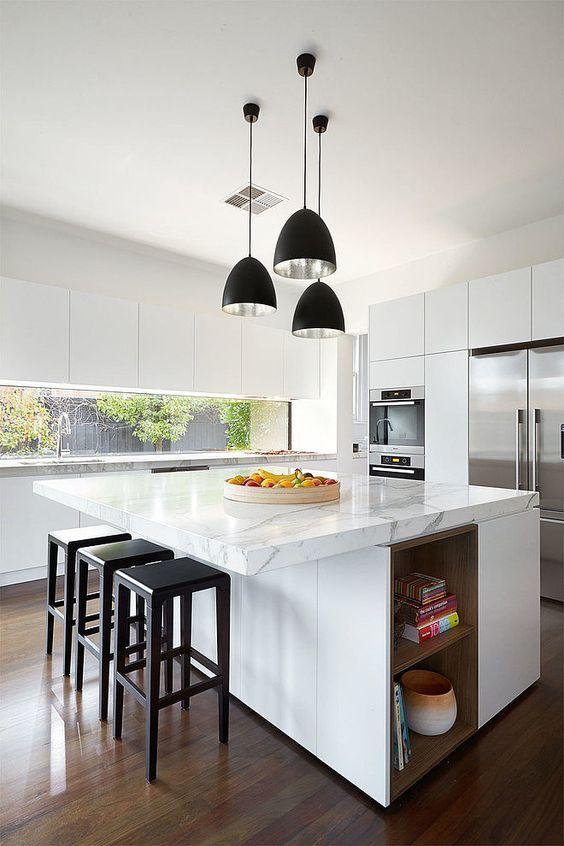 une cuisine contemporaine faite en blanc, avec un îlot de cuisine surdimensionné qui comprend du rangement et un comptoir pour manger en même temps