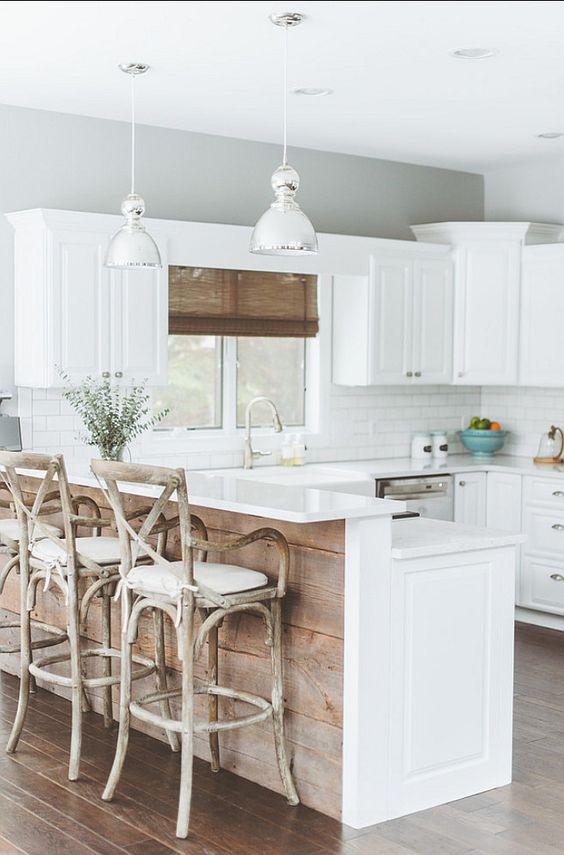 une cuisine de ferme blanche avec un îlot de cuisine doté d'un comptoir surélevé pour manger ici