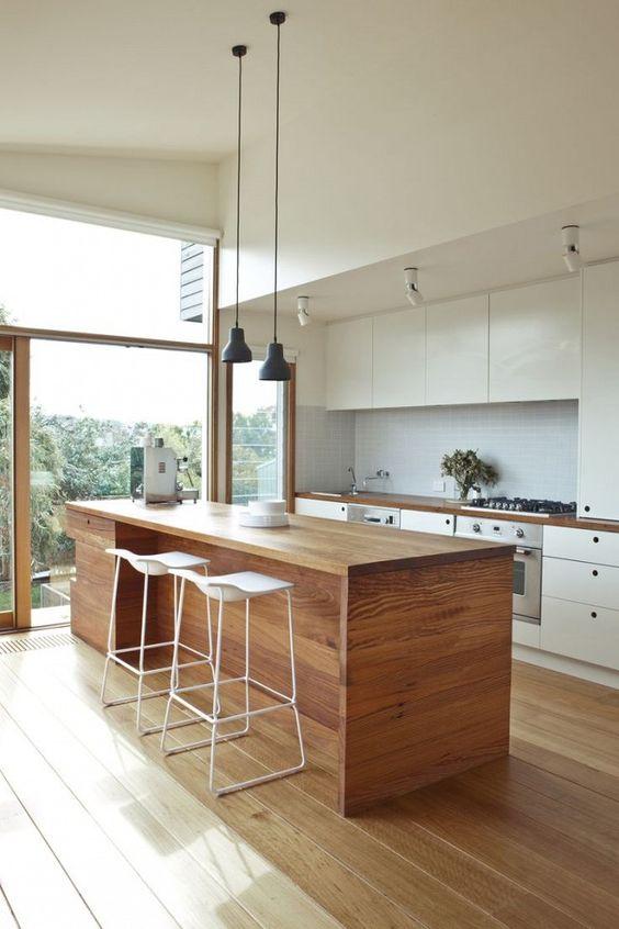 une cuisine moderne en blanc, avec un îlot de cuisine en bois qui est bon à la fois pour manger et cuisiner ici