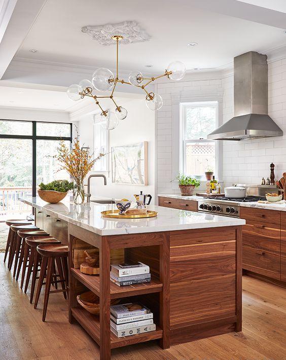 une grande cuisine de ferme avec de riches meubles teintés, un grand îlot de cuisine avec un coin salon et des rangements, aussi
