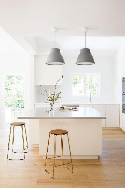 une cuisine scandinave lumineuse avec un grand îlot de cuisine doté d'un comptoir plus long pour manger confortablement ici