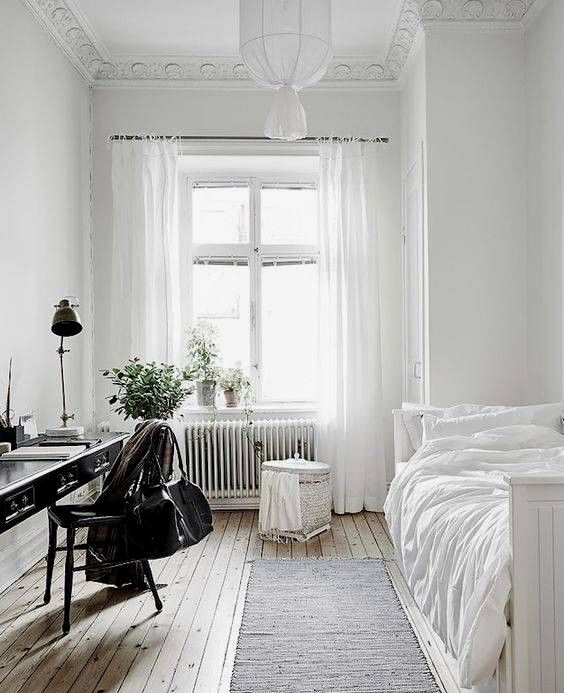 une chambre d'hôtes sereine et aérée avec beaucoup de blanc et un bureau noir vintage et une chaise pour se démarquer