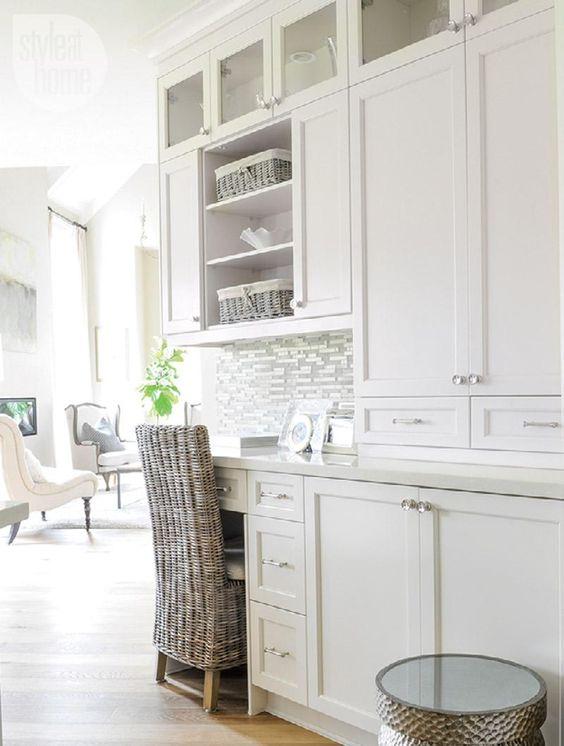 une cuisine rustique blanche avec un bureau intégré et une chaise tissée pour travailler ou découvrir