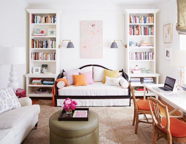 une chambre d'amis avec deux canapés convertibles comme espaces de couchage et un bureau à domicile partagé près de la fenêtre