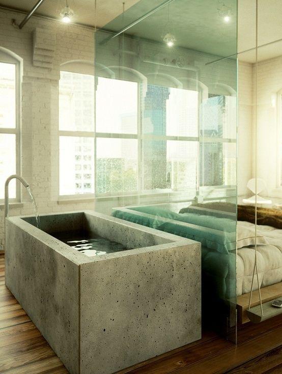 une chambre industrielle avec une baignoire en béton séparée par un séparateur en verre du lit