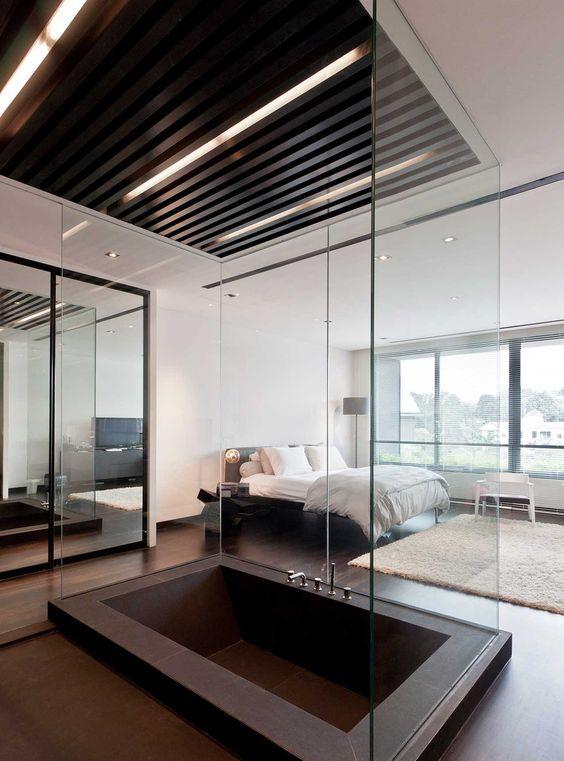 une chambre contemporaine avec une grande baignoire encastrée en métal sombre séparée par du verre pour éviter les éclaboussures au sol