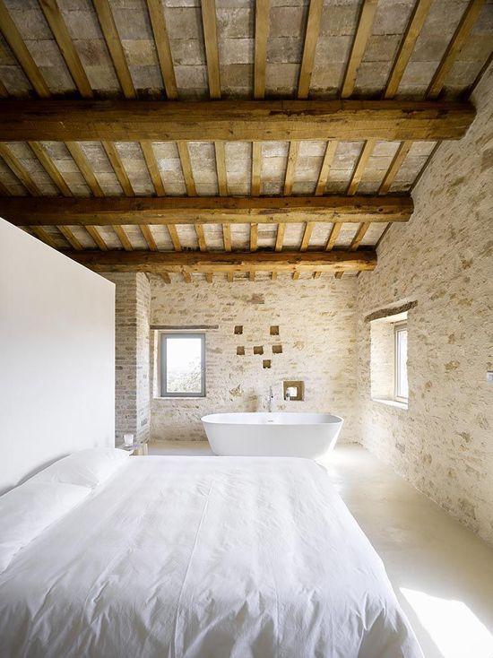 une chambre provençale rurale avec beaucoup de pierre et de bois et une baignoire près de la fenêtre pour profiter de la vue