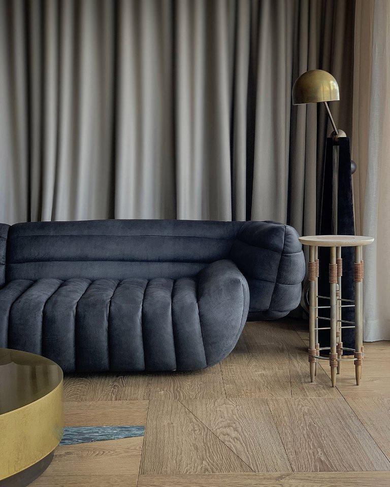Le salon dispose d'un mobilier contemporain raffiné, d'une table imparfaite fraîche et de lourds rideaux