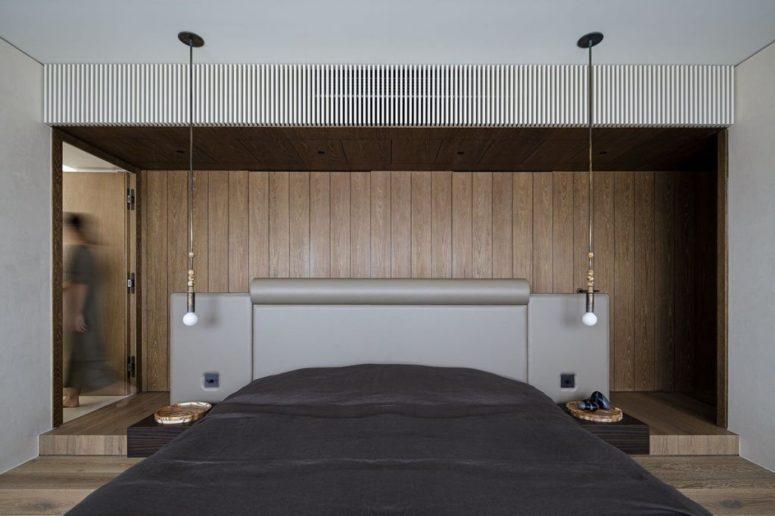 La chambre contemporaine est revêtue de bois, il y a des ampoules et un lit rembourré