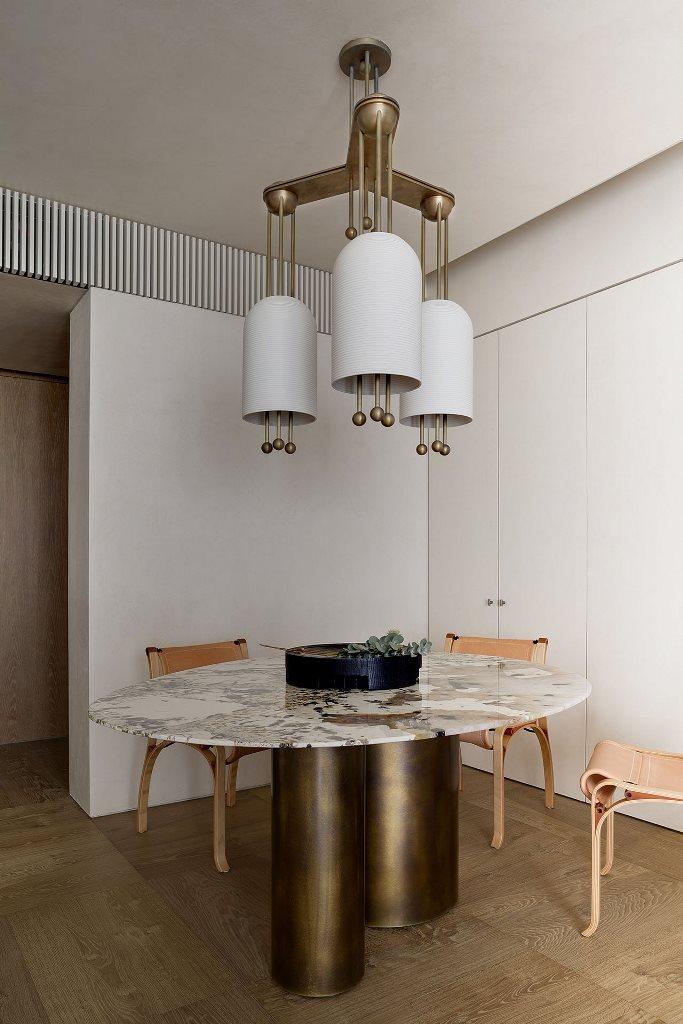L'espace salle à manger comprend une table unique avec un plateau en pierre, des chaises en cuir et un lustre audacieux