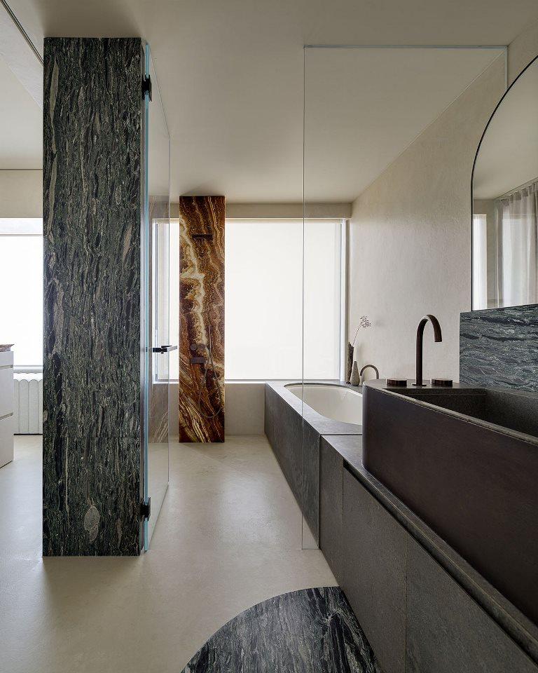 La salle de bain est faite avec une baignoire recouverte de pierre et une puanteur de pierre ainsi que de magnifiques piliers de marbre