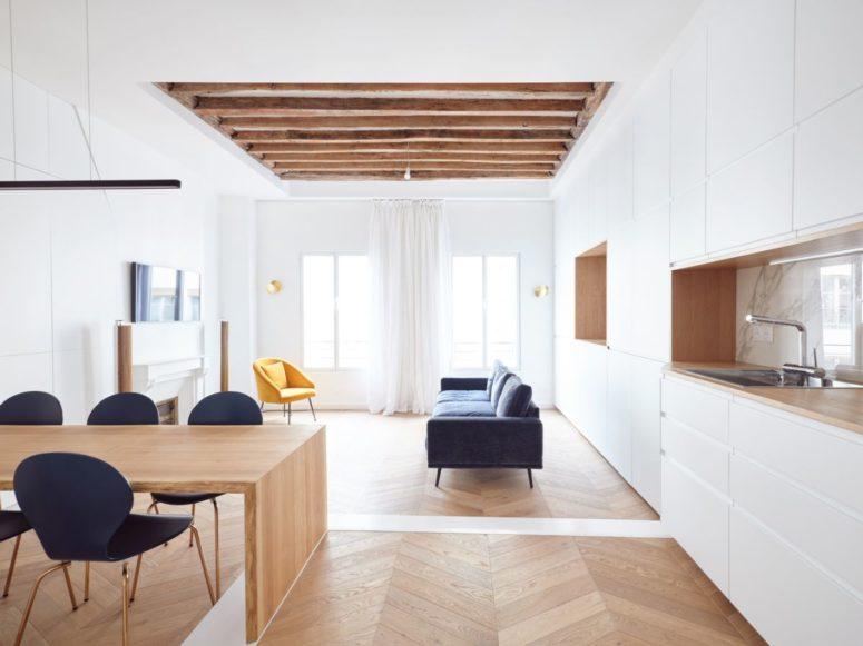 Le salon est fait avec une fausse cheminée, un canapé bleu, une chaise jaune et des rideaux aérés et légers, des poutres en bois au plafond ajoutent du confort