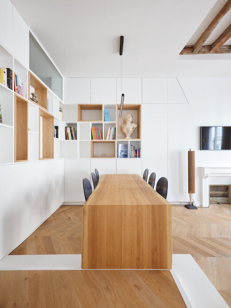 Il y a beaucoup d'unités de rangement, ouvertes et fermées élégantes, et la table à manger est une seule et longue dalle de bois