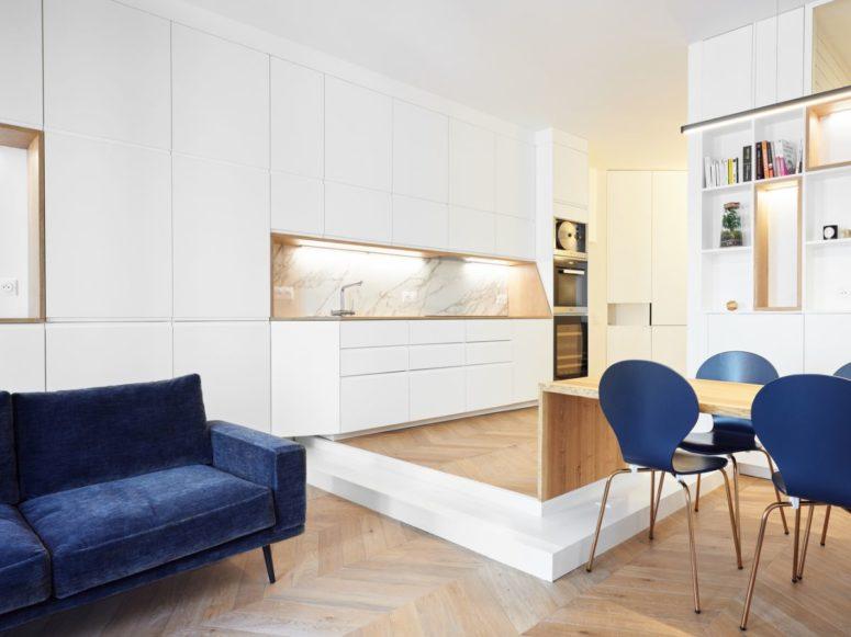 La cuisine ouverte est légèrement surélevée et cela ajoute une bordure claire autour d'elle, j'adore le dosseret en marbre blanc, c'est du pur luxe