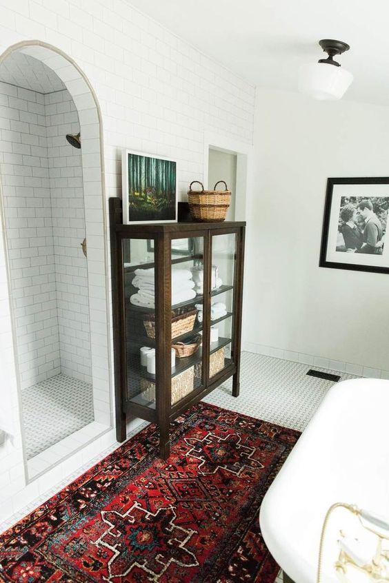 une salle de bain moderne avec un tapis lumineux, des carreaux blancs partout et une armoire en verre teinté foncé vintage