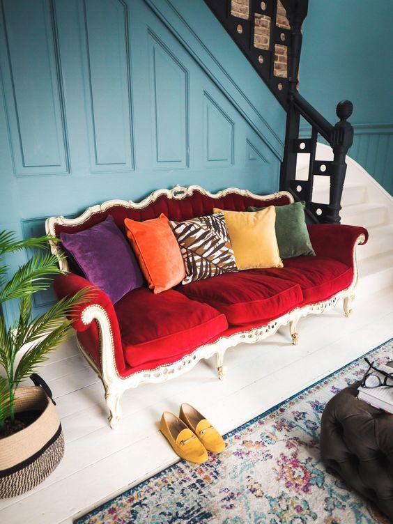 une entrée éclectique lumineuse complétée par un canapé rouge vintage audacieux et des oreillers colorés