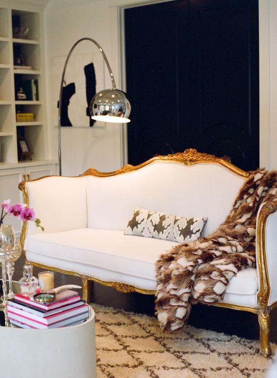 un espace contemporain contrasté agrémenté d'un beau canapé blanc vintage avec encadrement doré