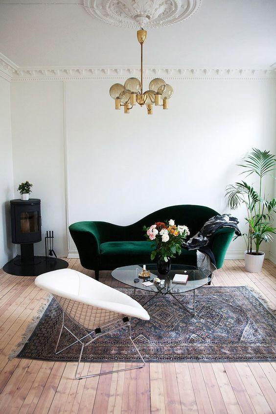 un canapé vintage en velours vert foncé et un médaillon au plafond pour ajouter un look chic à l'espace
