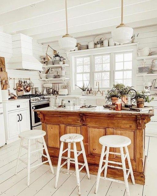 une cuisine blanc pur avec un îlot de cuisine vintage aux couleurs chaudes avec une forte sensation rustique en même temps