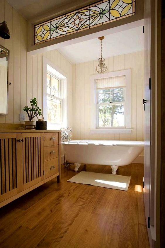 une salle de bain de ferme avec une baignoire sur pattes vintage blanche qui donne le ton à l'espace